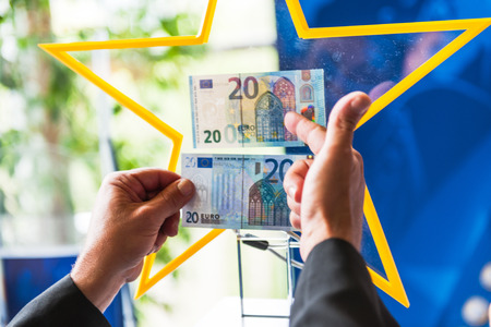 euro area: STRASBOURG, FRANCE - MAY 2, 2015: Comparing old and new 20 Euro banknotes by the European Central Bank official. The new 20 Euro banknote with the European symbol Europe is highly protected and has a new design and will start circulating in the euro area  Editorial