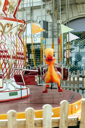merry go round: STRASBOURG FRANCE  MAY 23 2015: Duck toy in the seat of a colorful Merry Go Round