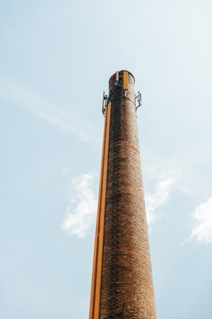 confined space: Industrial abandoned brick smoke stack against blue sky with telecommunication mobile phone 4g umts antenna on top