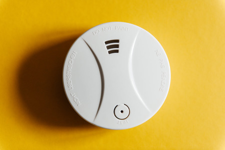 home interior: White smoke detector on yellow ceiling. A smoke detector is a device that senses smoke, typically as an indicator of fire.