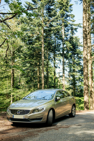 electric automobile: FRANCE  MAY 10 2015: Hybrid Volvo S60 executive car parked in the middle of green forest. Volvo Hybrid Electric Vehicle is considered one of the most safe and environmentally protective automobile