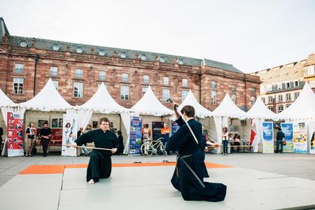 public demonstration: STRASBOURG FRANCE  APRIL 24 2015: Samurai sword public demonstration by two men wearing traditioanl samurai Hakama in PLace Kleber Strasbourg Alsace Eurometropole