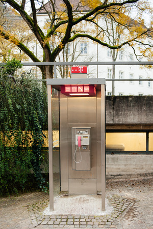 ag: BADENBADEN GERMANY  MOVEMBER 20 214: Deutsche Telekom AG payphone booth at dusk
