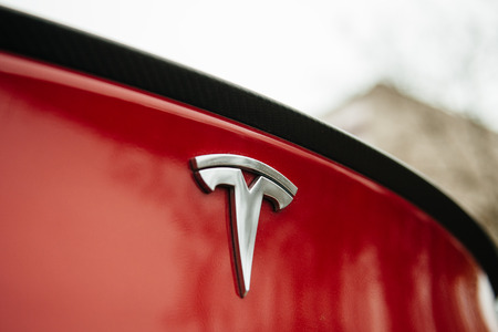 PARIS FRANCE  NOVEMBER 29: Tesla Motors logo on a red car. Tesla is an American company that designs manufactures and sells electric cars Editoriali