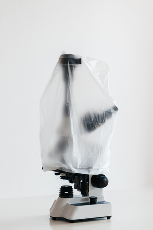 head protection: Miroscope with trinocular head and camera adapter in laboratory covered with dust protection plastic