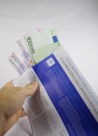 tax refund: ISTANBUL, TURKEY - FEBRUARY 06, 2011: Hand holding Tax Free envelope with thousands of euro in it after claiming back tax. Global Blue is a tourism shopping tax refund company headquartered in Nyon, Switzerland