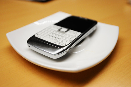personal data assistant: Old smartphone on white plate, with focus on the corner buttons Stock Photo