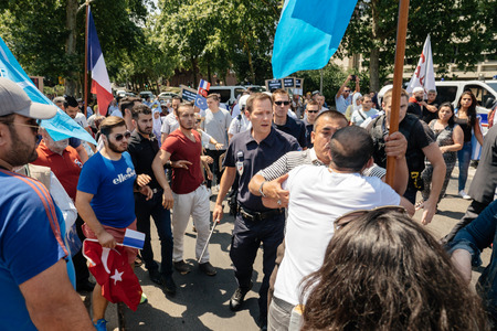clash: STRASBOURG, FRANCE - JULY 11, 2015: Police use force to prevent clash while Uyghur human rights activists participate in a demonstration to protest against Chinese governments policy in Uyghur