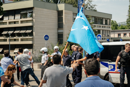 clash: STRASBOURG, FRANCE - JULY 11, 2015: Police use pepper spray to prevent clash - Uyghur human rights activists participate in a demonstration to protest against Chinese governments policy in Uyghur