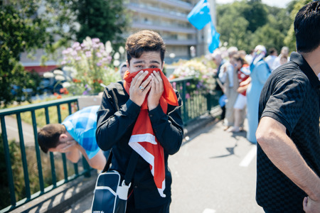 protestor: STRASBOURG, FRANCE - JULY 11, 2015: Protestor cries after being pepper sprayed - Uyghur human rights activists participate in a demonstration to protest against Chinese governments policy in Uyghur