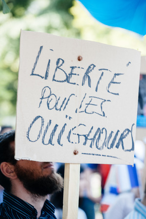 exile: STRASBOURG, FRANCE - JULY 11, 2015: Freedom for Uyghur - Uyghur human rights activists participate in a demonstration to protest against Chinese governments policy in Uyghur Editorial