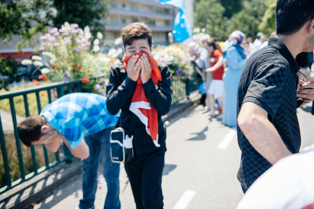 repression: STRASBOURG, FRANCE - JULY 11, 2015: Protestor cries after being pepper sprayed - Uyghur human rights activists participate in a demonstration to protest against Chinese governments policy in Uyghur