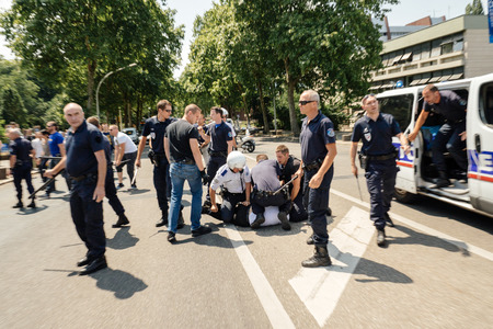 repression: STRASBOURG, FRANCE - JULY 11, 2015: Police arresting man - Uyghur human rights activists participate in a demonstration to protest against Chinese governments policy in Uyghur