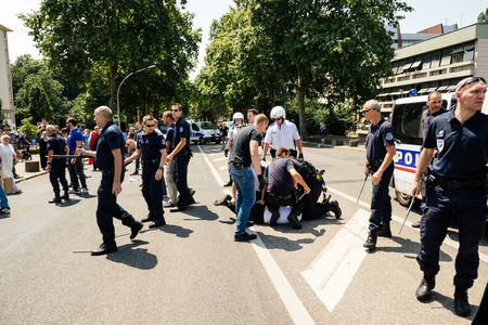 exile: STRASBOURG, FRANCE - JULY 11, 2015: Police arresting man - Uyghur human rights activists participate in a demonstration to protest against Chinese governments policy in Uyghur