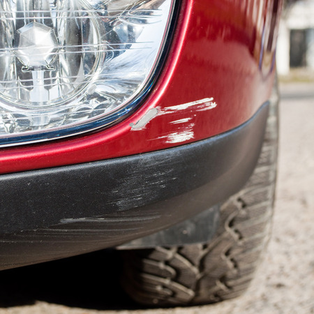 scratched: Scratch on a cars bumper - right under the headlight