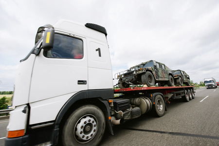flatbed truck: Frankfurt am Main, Germany - July 4, 2011: Truck carrying lightweight armored vehicles on a public highway. Editorial
