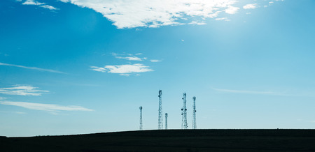 Five telecommunication mast TV antennas with blue sky and white clouds in the morning