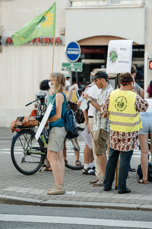 protesting: STRASBOURG, FRANCE - AUG 6, 2015: People wearing air masks protesting against air pollution in Strasbourg, Alsace, France - woman protesting at crossroad Editorial