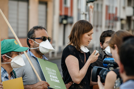 demonstrator: STRASBOURG, FRANCE - AUG 6, 2015: People wearing air masks protesting against air pollution in Strasbourg, Alsace, France - placard: I isolate my house,I save the climate