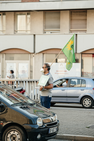 protesting: STRASBOURG, FRANCE - AUG 6, 2015: People wearing air masks protesting against air pollution in Strasbourg, Alsace, France - man holding European Green Party at intersection Editorial