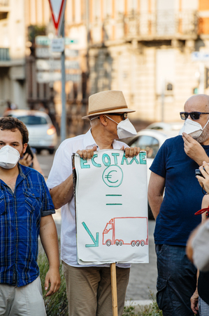 demonstrator: STRASBOURG, FRANCE - AUG 6, 2015: People wearing air masks protesting against air pollution in Strasbourg, Alsace, France - man holding placard higher ecotaxe menas less trucks