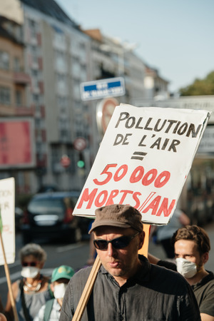 protesting: STRASBOURG, FRANCE - AUG 6, 2015: People wearing air masks protesting against air pollution in Strasbourg, Alsace, France - man protesting with placard: 50000 dies yearly from pollution