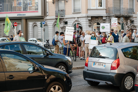 protesting: STRASBOURG, FRANCE - AUG 6, 2015: People wearing air masks protesting against air pollution in Strasbourg, Alsace, France - crowd protesting at busy crossroad