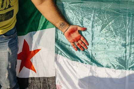 syrian war: STRASBOURG, FRANCE - AUG 20, 2015: People protesting in front of European Parliament denouncing the Syrian airstrikes on a Damascus suburb of Douma which killed more than 80 people - syrian war Tattoo on hand and Syrian flag Editorial