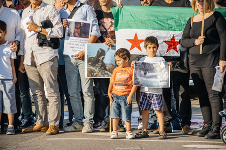 political and social issues: STRASBOURG, FRANCE - AUG 20, 2015: People protesting in front of European Parliament denouncing the Syrian airstrikes on a Damascus suburb of Douma which killed more than 80 people - kid holding war placard Editorial