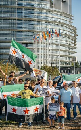 political and social issues: STRASBOURG, FRANCE - AUG 20, 2015: People protesting in front of European Parliament denouncing the Syrian airstrikes on a Damascus suburb of Douma which killed more than 80 people waving Syrian flag and placards