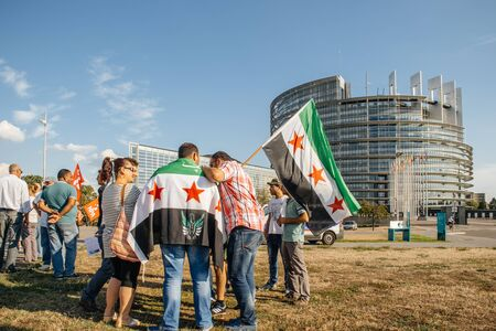 political and social issues: STRASBOURG, FRANCE - AUG 20, 2015: People protesting in front of European Parliament denouncing the Syrian airstrikes on a Damascus suburb of Douma which killed more than 80 people - flag of Syria with Parliament building in the background Editorial