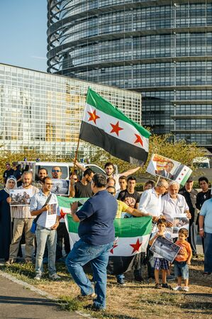 bombardment: STRASBOURG, FRANCE - AUG 20, 2015: People protesting in front of European Parliament denouncing the Syrian airstrikes on a Damascus suburb of Douma which killed more than 80 people waving Syrian flag