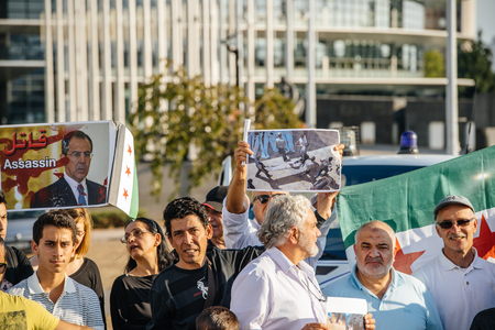 european parliament: STRASBOURG, FRANCE - AUG 20, 2015: People protesting in front of European Parliament denouncing the Syrian airstrikes on a Damascus suburb of Douma which killed more than 80 people - Sergey lavrov killer placard