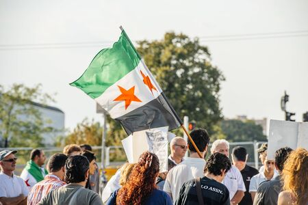 political and social issues: STRASBOURG, FRANCE - AUG 20, 2015: People protesting in front of European Parliament denouncing the Syrian airstrikes on a Damascus suburb of Douma which killed more than 80 people - waving syrian flag Editorial