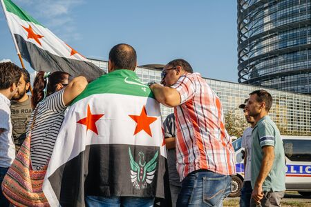 political and social issues: STRASBOURG, FRANCE - AUG 20, 2015: People protesting in front of European Parliament denouncing the Syrian airstrikes on a Damascus suburb of Douma which killed more than 80 people - people holding wearing Syrian flag