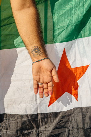 political and social issues: STRASBOURG, FRANCE - AUG 20, 2015: People protesting in front of European Parliament denouncing the Syrian airstrikes on a Damascus suburb of Douma which killed more than 80 people - syrian war Tattoo on hand and Syrian flag Editorial