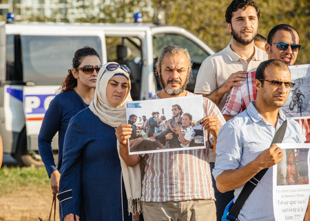 syrian war: STRASBOURG, FRANCE - AUG 20, 2015: People protesting in front of European Parliament denouncing the Syrian airstrikes on a Damascus suburb of Douma which killed more than 80 people - holding war photography Editorial