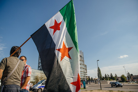 political and social issues: STRASBOURG, FRANCE - AUG 20, 2015: People protesting in front of European Parliament denouncing the Syrian airstrikes on a Damascus suburb of Douma which killed more than 80 people - man holding flag of Syria Editorial