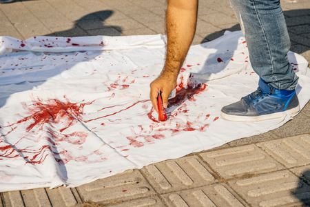european parliament: STRASBOURG, FRANCE - AUG 20, 2015: People protesting in front of European Parliament denouncing the Syrian airstrikes on a Damascus suburb of Douma which killed more than 80 people - blood immitation on white tissue