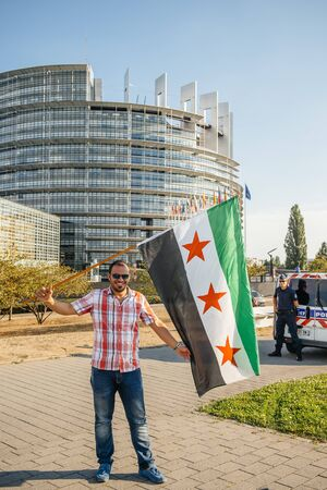 european parliament: STRASBOURG, FRANCE - AUG 20, 2015: People protesting in front of European Parliament denouncing the Syrian airstrikes on a Damascus suburb of Douma which killed more than 80 people - man holding syrian flag Parliament building in the background