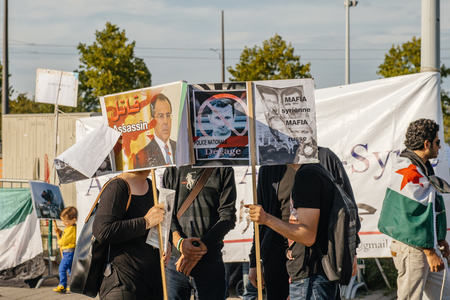 mafia: STRASBOURG, FRANCE - AUG 20, 2015: People protesting in front of European Parliament denouncing the Syrian airstrikes on a Damascus suburb of Douma which killed more than 80 people - placard syrian mafia equal russian mafia