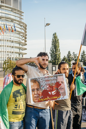 regime: STRASBOURG, FRANCE - AUG 20, 2015: People protesting in front of European Parliament denouncing the Syrian airstrikes on a Damascus suburb of Douma which killed more than 80 people - down with the Assad and Lavrov regime