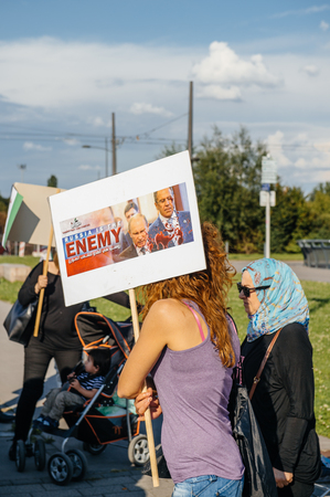 political and social issues: STRASBOURG, FRANCE - AUG 20, 2015: People protesting in front of European Parliament denouncing the Syrian airstrikes on a Damascus suburb of Douma which killed more than 80 people - Russia is the enemy placard Editorial