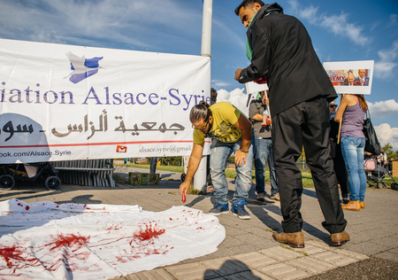 political and social issues: STRASBOURG, FRANCE - AUG 20, 2015: People protesting in front of European Parliament denouncing the Syrian airstrikes on a Damascus suburb of Douma which killed more than 80 people - blood immitation on white scarf