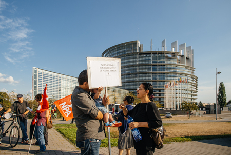 political and social issues: STRASBOURG, FRANCE - AUG 20, 2015: People protesting in front of European Parliament denouncing the Syrian airstrikes on a Damascus suburb of Douma which killed more than 80 people - we are solidare with Syrian people placard Editorial