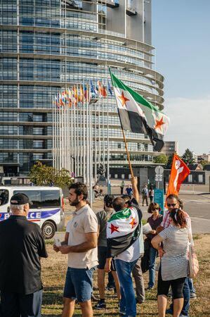 political and social issues: STRASBOURG, FRANCE - AUG 20, 2015: People protesting in front of European Parliament denouncing the Syrian airstrikes on a Damascus suburb of Douma which killed more than 80 people - waving flag of Syria European Parliament