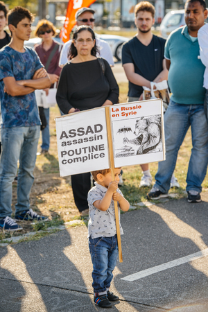 political and social issues: STRASBOURG, FRANCE - AUG 20, 2015: People protesting in front of European Parliament denouncing the Syrian airstrikes on a Damascus suburb of Douma which killed more than 80 people - Assad assassin, Putin complicit