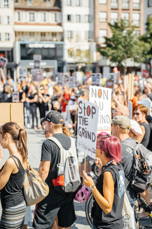 outcry: STRASBOURG, FRANCE - AUG 22, 2015: Marine conservation non-profit organization Sea Shepherd protesting against the slaughter of pilot whales and arrest of 7 crew members - placard stop the grind