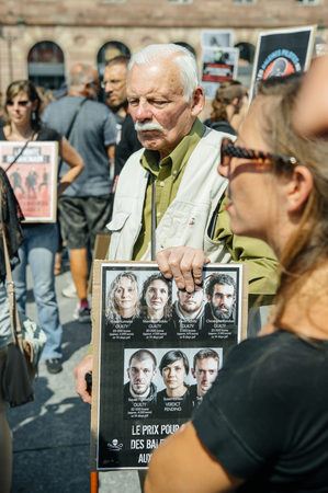 outcry: STRASBOURG, FRANCE - AUG 22, 2015: Marine conservation non-profit organization Sea Shepherd protesting against the slaughter of pilot whales and arrest of 7 crew members - man holding placard with arested people
