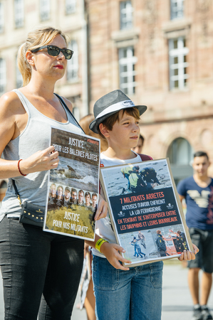 son in law: STRASBOURG, FRANCE - AUG 22, 2015: Marine conservation non-profit organization Sea Shepherd protesting against the slaughter of pilot whales and arrest of 7 crew members - mom and son protesting Editorial